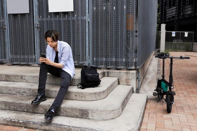 スマートフォンを使用して市内の電動自転車を持つ男