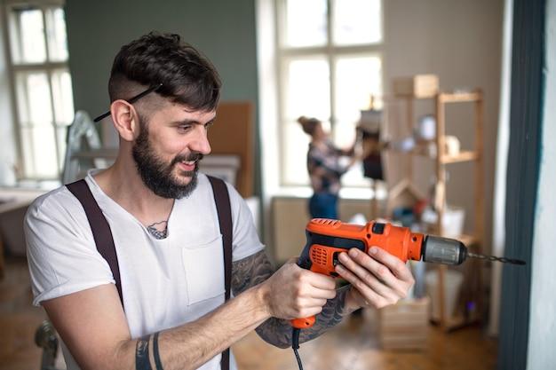 집에서 전기 드릴을 사용하는 남자, 재배치 및 diy 개념.