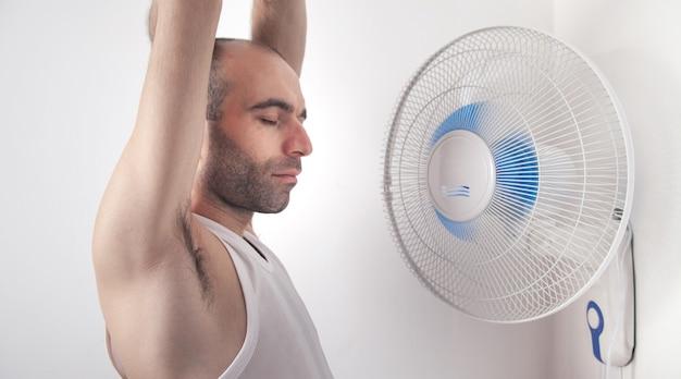 家に扇風機を持つ男