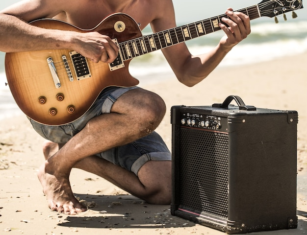Man with electric guitar on the beach