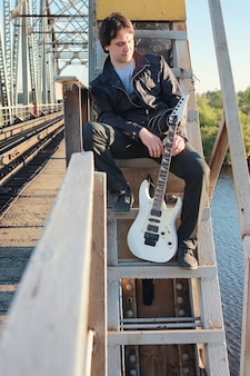 A man with an electric guitar in the industrial landscape outdoors