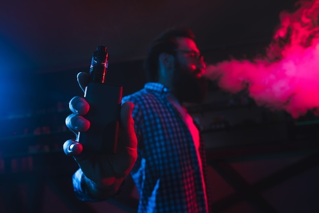 Man with an electronic cigarette in his hands produces smoke