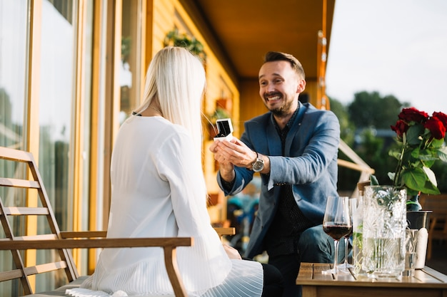 Man with engagement ring making proposal of marriage to woman