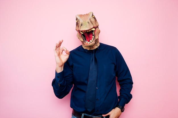 Man with euphoric dinosaur head and fingers with ok symbol