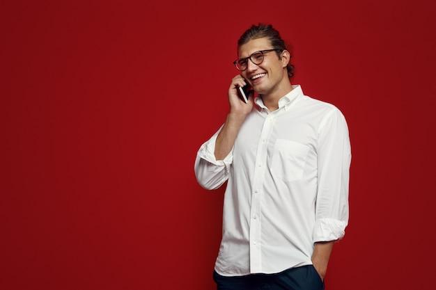 빨간 벽에 서있는 동안 스마트 폰에 안경을 가진 남자
