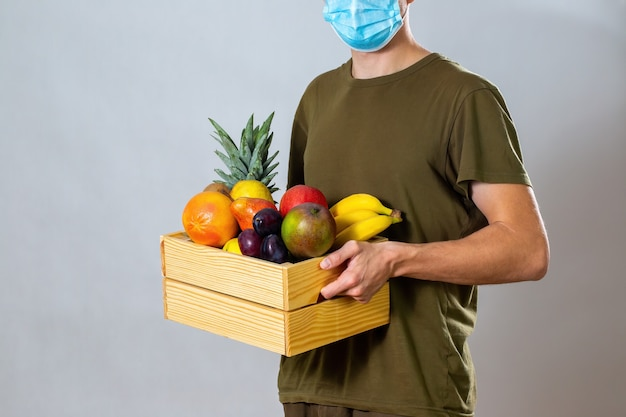 Man with face mask giving wooden box with fruit and vegetable to customer.