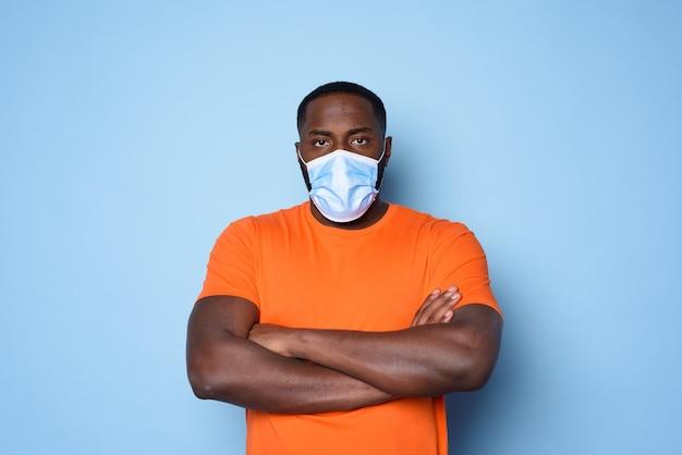 У человека в маске много вопросов и сомнений по поводу covid 19. голубой фон.