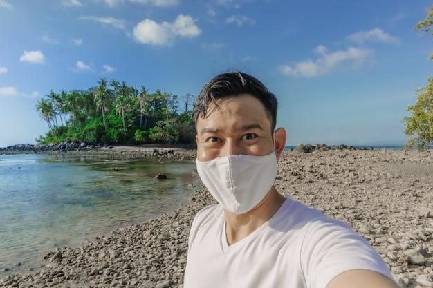 フェイスマスクを持った男がパンデミックで夏の海の旅を
