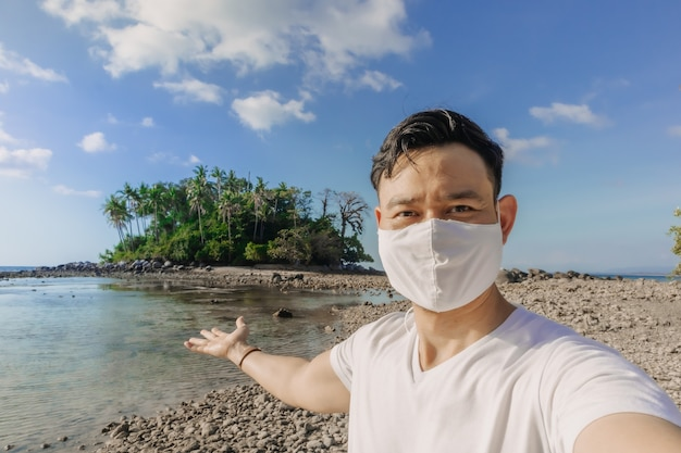 フェイスマスクをした男性は、covidパンデミックの最中に夏の海旅行をします
