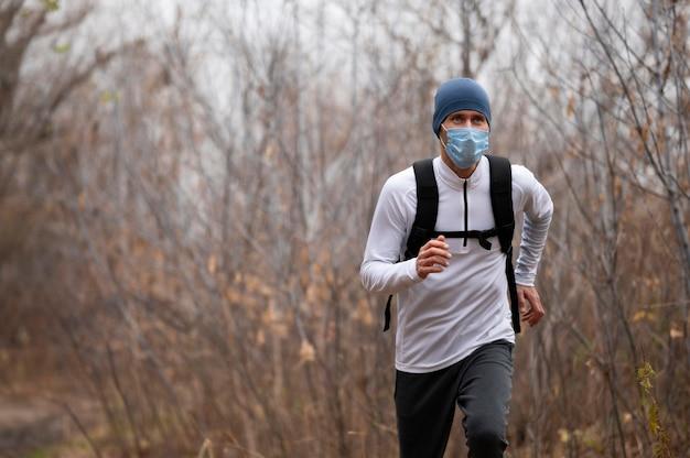 Человек с маской для лица в лесу работает