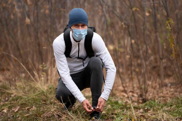 靴ひもを結ぶ森の中でフェイスマスクを持つ男
