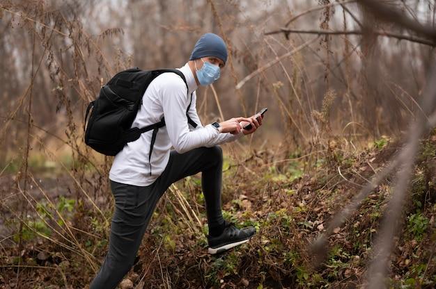 森の中でフェイスマスクを持つ男