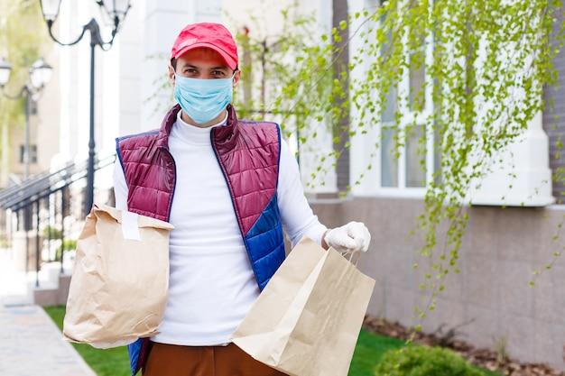 얼굴 마스크를 쓴 남자가 바이러스 전염병 동안 음식과 식료품을 배달하고 있습니다.