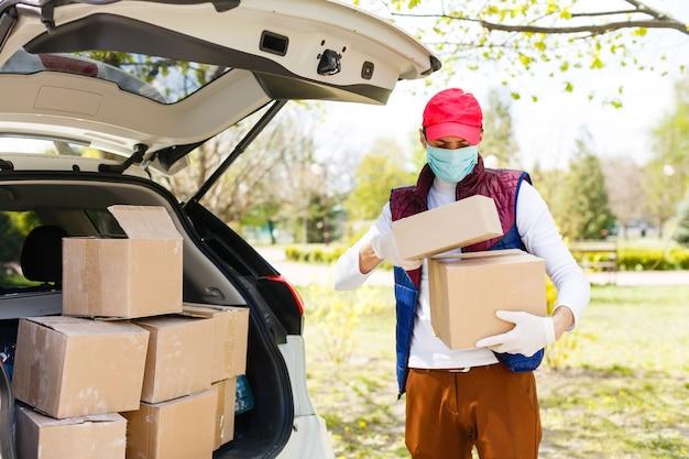 フェイスマスクを持った男性が、ウイルスの流行中に食料や食料品を配達しています。