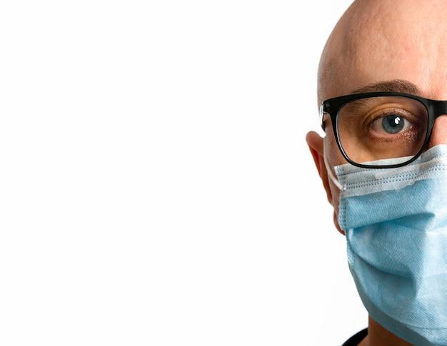 フェイスマスクを持つ男を白で隔離します。