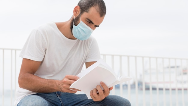 Man with face mask outdoors reading book with copy space