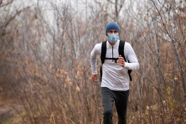 森の中を走っているフェイスマスクを持つ男