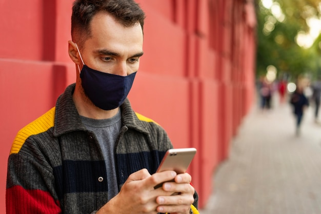 Uomo con maschera facciale e concetto di distanza sociale