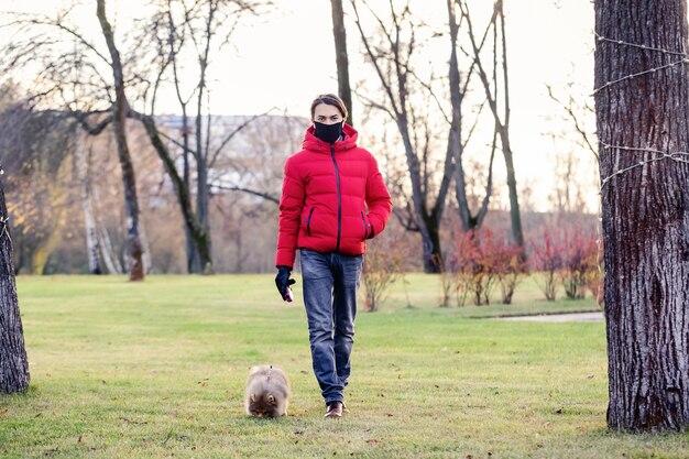 フェイスマスクを持った男がコロナウイルスの最中に犬を家の近くに散歩に連れて行く