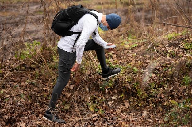Uomo con la maschera per il viso a piedi attraverso i boschi