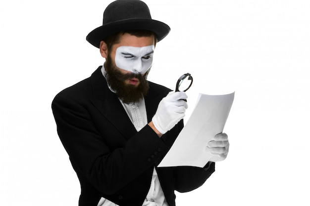Man with a face mime reading through magnifying glass