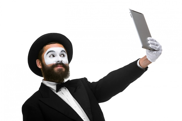 Man with a face mime working on a laptop isolated on a white
