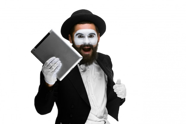Man with face mime working a laptop isolated on white