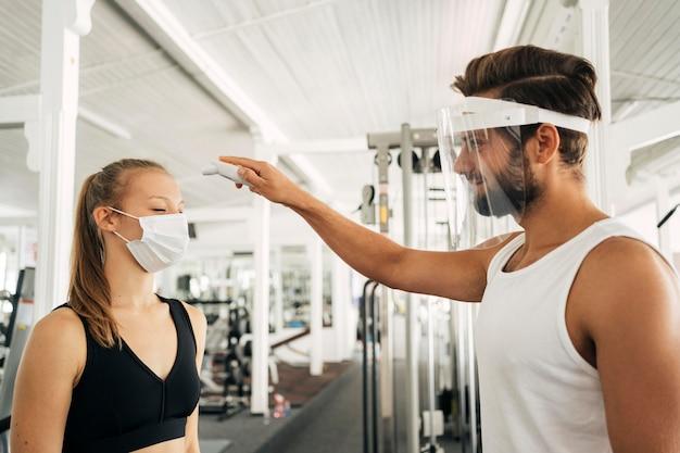 Мужчина с маской для лица проверяет температуру женщины в тренажерном зале