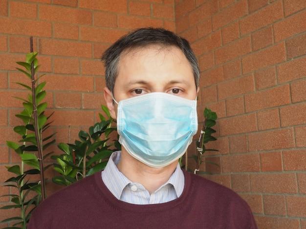 呼吸器系の病気の感染拡大を止めるためのフェイスマスクを持つ男