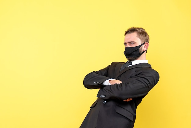 Man with facial mask focusing onnd thinking about one important issue over yellow