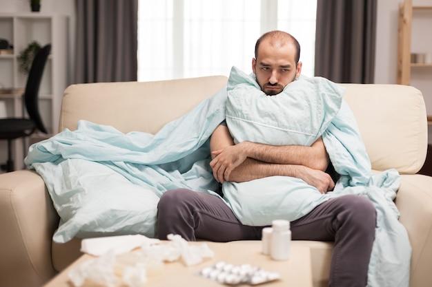 Человек с лихорадкой, завернутый в одеяло, сидит на диване во время самоизоляции.
