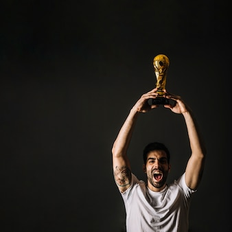 Man with FIFA trophy celebrating victory