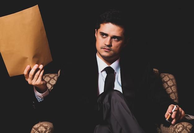 Человек с файлом сидит в винтажном кресле