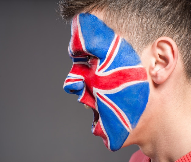 A man with a flag on his face supports the uk in sports.