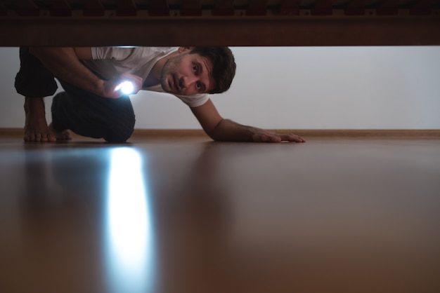 The man with a flashlight looking under the bed