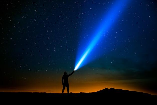 별이 빛나는 하늘을 가리키는 손전등을 가진 남자