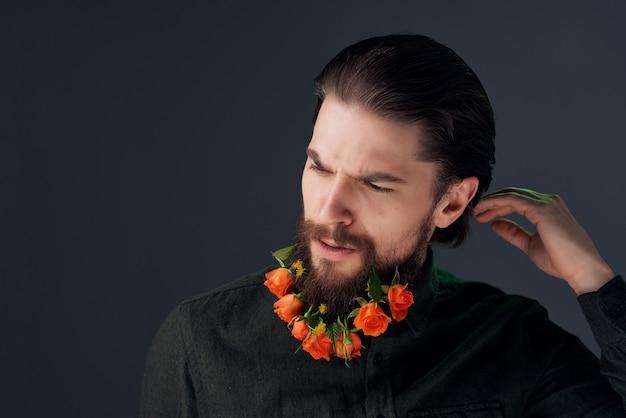 クローズアップスタジオをポーズするひげの装飾の花を持つ男。高品質の写真