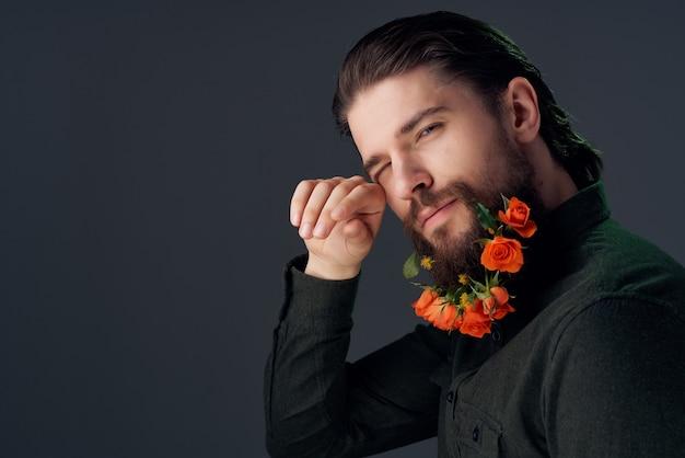 クローズアップスタジオポーズのひげの装飾の花を持つ男