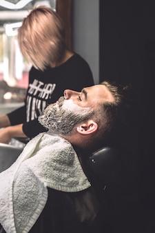 Uomo con la schiuma sul viso nel negozio di barbiere