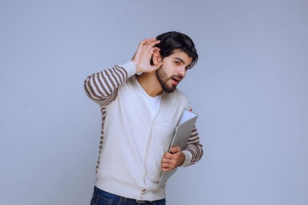 耳が聞こえないので耳を向けているフォルダーを持つ男。 無料写真