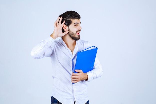 Uomo con cartella che punta l'orecchio per sentire bene