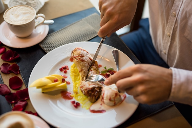 Man with fork and knife cutting delicious fresh dessert in restaurant