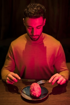 Man with fork and knife at table with model of heart on plate