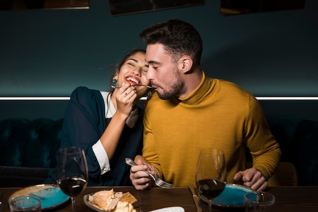 Man with fork in mouth near cheerful woman at table with glasses of wine and food in restaurant