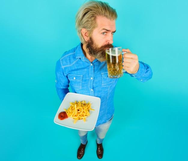 감자 튀김, 케첩, 맥주 한 잔을 가진 남자. 감자 튀김과 수염 난 남자입니다. 패스트 푸드, 건강에 해로운 식사, 정크 푸드.
