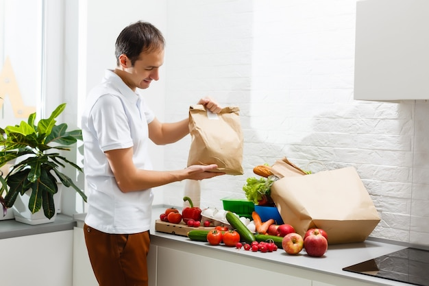 테이블 실내, 근접 촬영에 신선한 제품을 가진 남자. 음식 배달 서비스