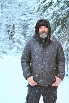 Человек с замерзшим лицом и бородой в зимнем лесу в сильный мороз
