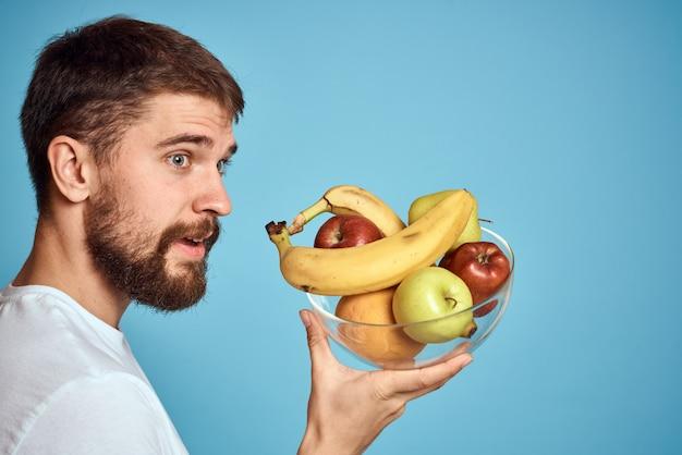 青の白いtシャツに果物を持つ男