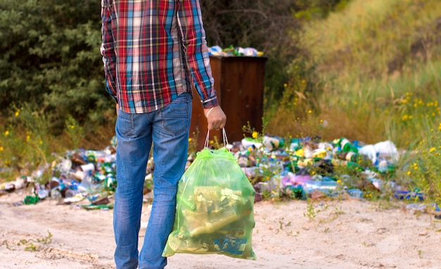 A man with a garbage bag cleans the area of garbage