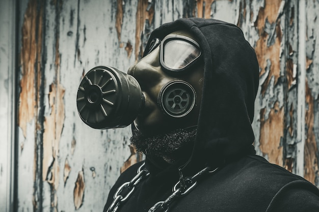 Man with gas mask and a hammer in machine room. nuclear, biological and chemical danger concept.